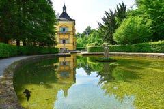 Pond in Public Gardens of Hellbrunn Palace Schloss Hellbrunn in Salzburg. Salzburg, Austria - May 25, 2019 : sculptures at the pond in Public Gardens of stock images