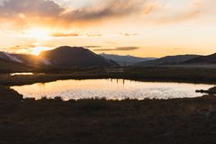 A pond reflection and landscape, sunset view at Independence Pass near Aspen, Colorado. A landscape, sunset view of the mountains and a pond reflection at royalty free stock photo