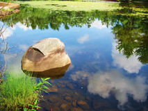 Pond with rock. Reflecting sky with clouds royalty free stock photography