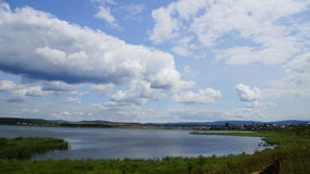 A pond and sky with clouds. Lake in the Republic of Bashkortostan Royalty Free Stock Photography