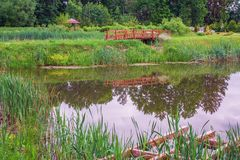 Pond in the summer park. Summer day at the picturesque lake in the park with a bridge and a gazebo stock photography