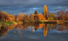 Pond and trees with colorful leaves on the bank in the afternoon in autumn. stock photography