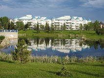 Pond and white house, Edmonton, Canada. White house with blue roof at the pond. Mill Woods Town Centre. Southeast Edmonton, Alberta, Canada Stock Images