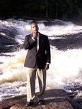 Pondering. Business man in a suit standing and thinking in front of a rushing river stock photo