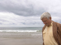 Pondering. Elderly man pondering by the ocean Stock Image