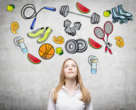 Pondering beautiful lady is thinking about her choice of sport activity. Royalty Free Stock Image