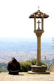 Pondering Franciscan monk near crucifix, Italy Royalty Free Stock Photo