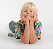 Pondering kid. Little blond boy laying on floor with hands on chin staring in a pondering doubtful mood at the camera Royalty Free Stock Photo