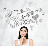 Pondering woman is thinking about her choice of sport activity. Sport icons are drawn on the concrete wall. Royalty Free Stock Photo
