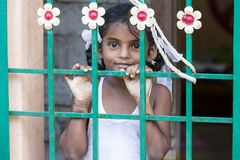 Closeup portrait of shy timid young pretty Indian girl child looking away and behind gate. Freedom concept. stock photography