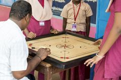 Documentary editorial image. Children playing carrom at the table. the concept of childhood and board games, brain development and Royalty Free Stock Photos