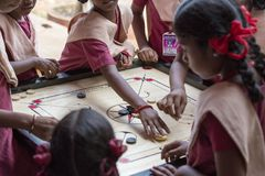 Documentary editorial image. Children playing carrom at the table. the concept of childhood and board games, brain development and Stock Photography