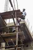 Documentary editorial image. An unidentified man works at heights. Very insecure scaffoldings. PONDICHERY, PUDUCHERY, INDIA - SEPTEMBER 04, 2017. An unidentified Royalty Free Stock Images