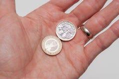 Pondmuntstuk en één Euro muntstuk die in een personenhand worden gehouden royalty-vrije stock afbeelding