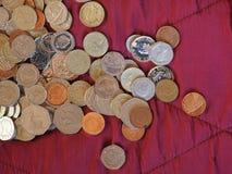 Pondmuntstukken, het Verenigd Koninkrijk over rode fluweelachtergrond Stock Afbeeldingen