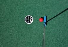 Pondo a bola sobre um mini campo de golfe imagens de stock