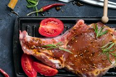 Pondo de conserva costeletas de cordeiro cruas com especiarias, o mel e o tomate na grade filtram, fecham-se acima fotografia de stock royalty free