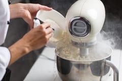 Pondo a farinha no misturador Fotografia de Stock