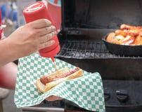Pondo a ketchup sobre um hotdog Fotos de Stock