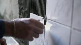 Pondo o azulejo sobre a parede filme