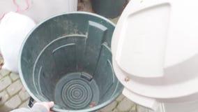 Pondo o lixo no recipiente do balde do lixo video estoque