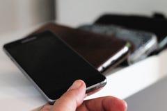 Pondo o smartphone sobre a prateleira Imagem de Stock Royalty Free