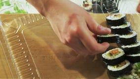 Pondo o sushi Rolls em um escaninho video estoque