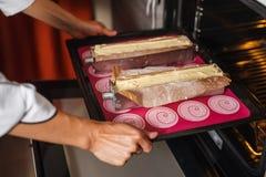 Pone las tortas en el horno Imagen de archivo