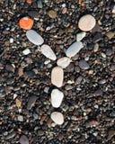 Pone letras al alfabeto puesto en una arena negra Y Imagen de archivo libre de regalías