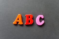 Pone letras al ` del ABC del ` de letras magnéticas plásticas en fondo gris Foto de archivo