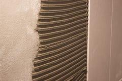 Ponendo le piastrelle di ceramica sul mortaio del cemento la distribuzione della soluzione ha calcolato la spatola sulla parete p fotografie stock libere da diritti