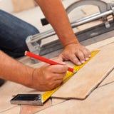 Ponendo le piastrelle per pavimento ceramiche - equipaggi le mani che segnano le mattonelle da tagliare, c Fotografie Stock