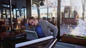 Ponente joven que habla con el cliente por la tableta, los teléfonos de las auriculares y el micrófono en el café almacen de metraje de vídeo