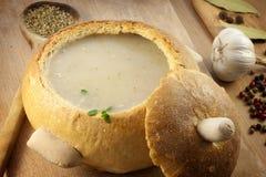_poner crema sopa en pan placa Fotografía de archivo