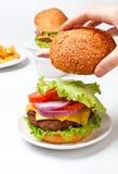 Poner el bollo superior en un cheeseburger Foto de archivo