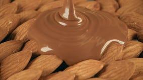 Poner el chocolate derretido sobre las almendras crudas almacen de video