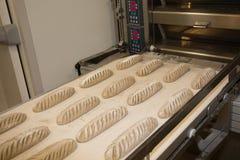 Poner el pan cocido fresco en el estante Proceso de fabricación del pan español Foto de archivo