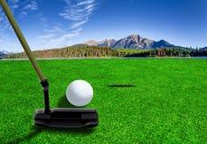 Poner la pelota de golf en un campo de golf hermoso imagenes de archivo