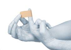 Poner un pequeño emplasto adhesivo en un dedo. Imagenes de archivo