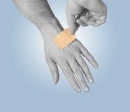 Poner un pequeño pegamento, vendaje en un brazo imágenes de archivo libres de regalías