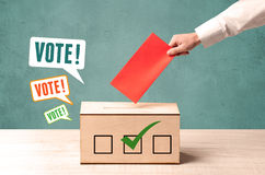 Poner un resbalón de votación en una urna Imagen de archivo