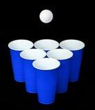 Pong da cerveja. Copos e bola plásticos azuis do pong do sibilo sobre o preto Fotografia de Stock