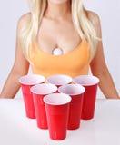 Pong de la cerveza. Tazas plásticas rojas con la bola de ping-pong y la muchacha rubia en top sin mangas atractivo Imagen de archivo