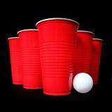 Pong de la cerveza. Tazas y bola de ping-pong plásticas rojas sobre negro Fotografía de archivo