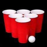 Pong de la cerveza. Tazas y bola de ping-pong plásticas rojas sobre negro Imagen de archivo