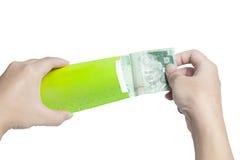 Ponga el dinero en el paquete verde Foto de archivo libre de regalías