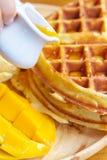 Ponga el jarabe en la galleta con el mango y el helado en el tablero de madera Imagen de archivo