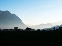 Ponga en contraste entre las montañas y los árboles por la mañana Foto de archivo libre de regalías