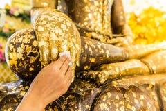 Ponga la hoja de oro sobre la estatua de Buda para dorar Imagen de archivo libre de regalías
