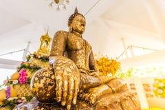 Ponga la hoja de oro sobre la estatua de Buda para dorar Qué gente utiliza t Fotos de archivo libres de regalías